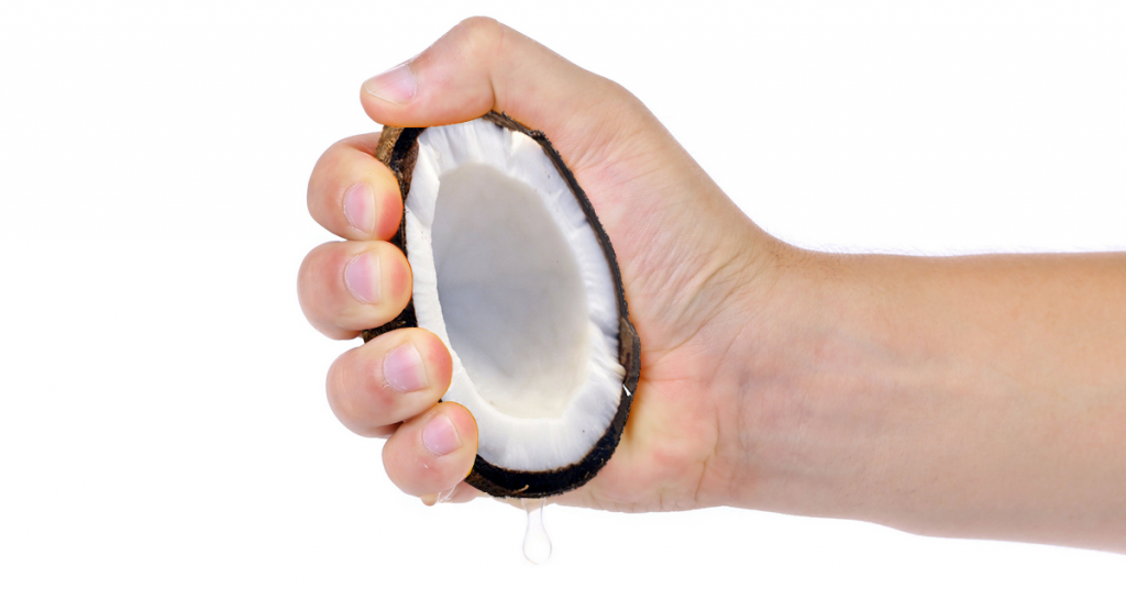 A hand squeezing coconut oil out of a half coconut